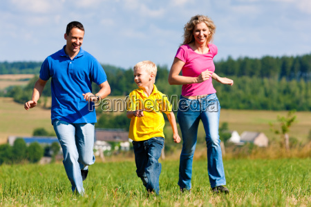 family playing in the meadow