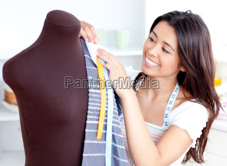 glowing young woman working with clothes