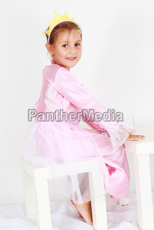 adorable girl dressed as princess playing