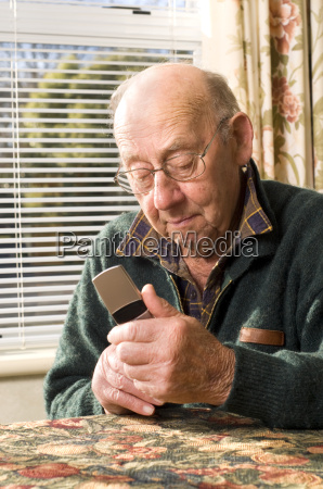 senior man texting and calling with
