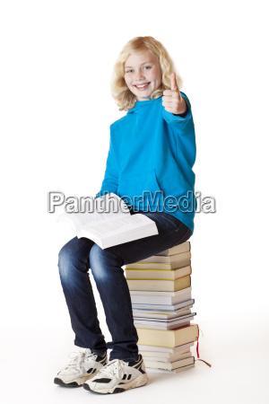 happy schoolgirl shows thumb and sitting