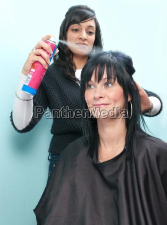 hair stylist sprays customer039s hair