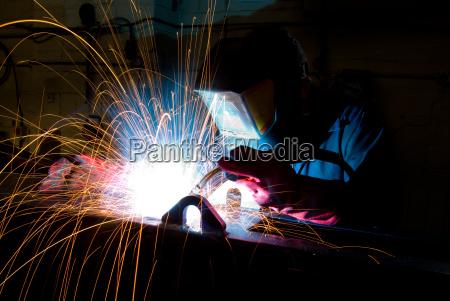 welder constructs steel box section