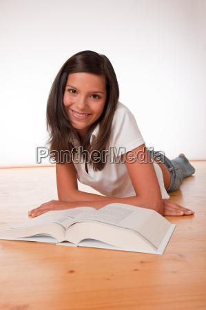 brown hair teenager lying on wooden