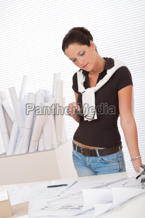 young female architect studying plans at