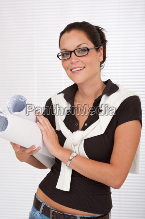 smiling female architect with glasses holding