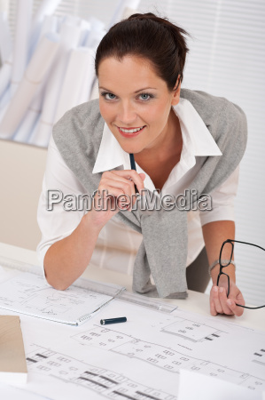smiling female architect with plans