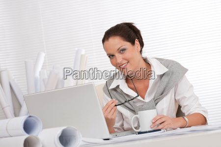 smiling female architect with laptop and