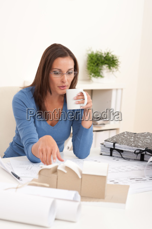 young female architect holding cup of