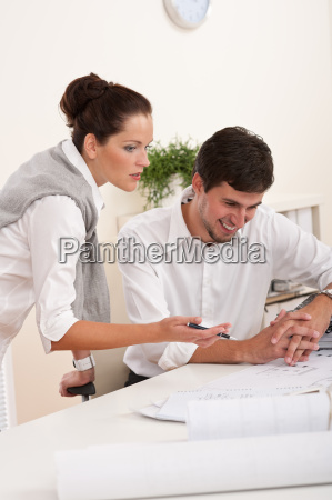 young man and woman working together