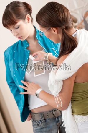 model fitting by female fashion designer