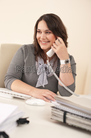 smiling secretary on phone at office