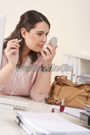 young executive woman applying lipstick at