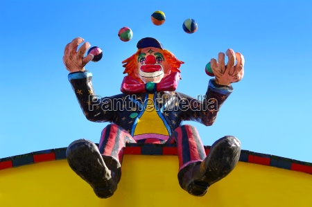 clown juggles while sitting on the