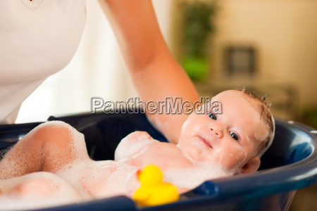 mother bathing her baby