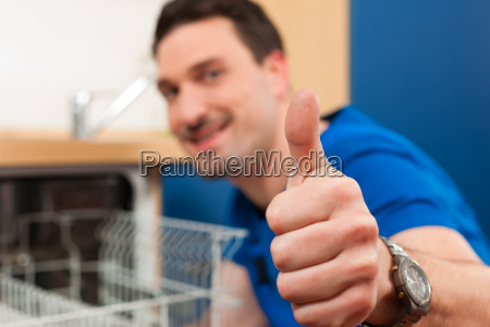 technician repairs the dishwasher