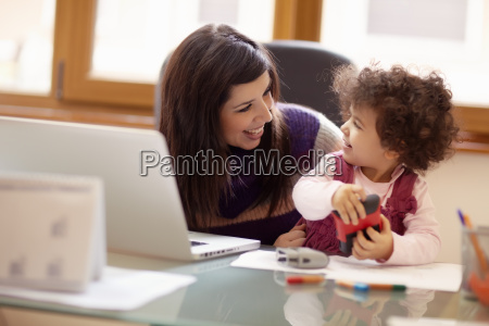 multitasking mother with her daughter
