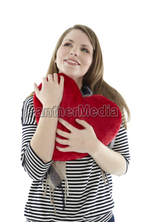 woman snuggles with a heart pillow