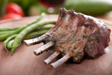 grilled lamb crown on wooden board