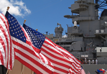 us flags flying beside the battleship