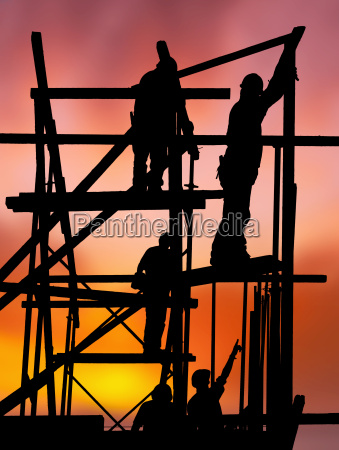 construction workers against colorful sunset