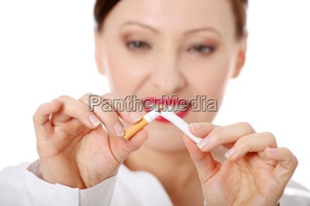 mature woman breaking cigarette