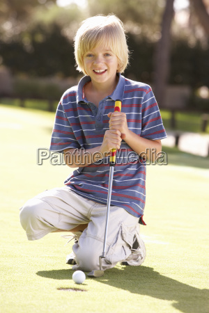 young boy practising golf on putting