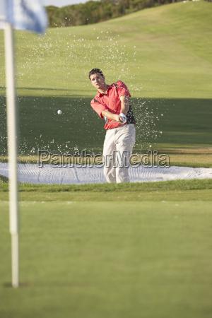 male golfer playing bunker shot on