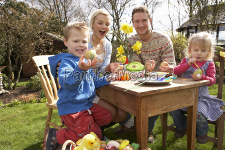 family decorating easter eggs on table