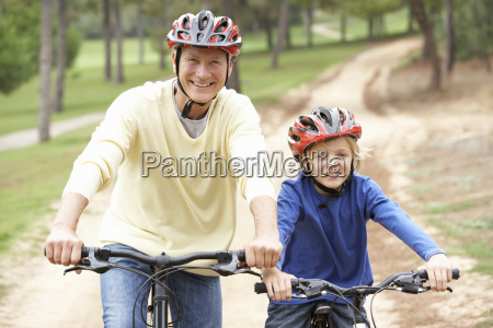 grandfather and grandson riding bicycle in