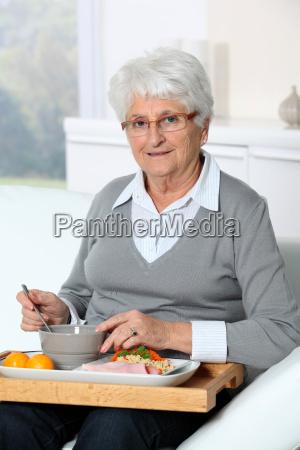 elderly woman sitting in sofa