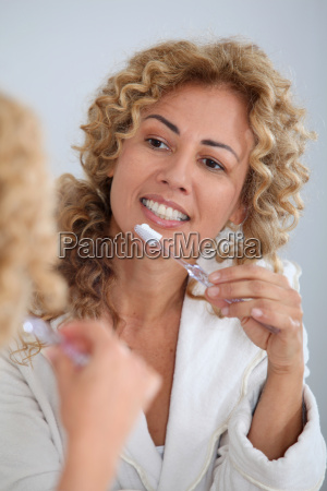 portrait of woman brushing her teeth