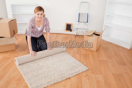 attractive woman rolling up a carpet