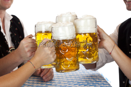 bavarian men and women clinking beer