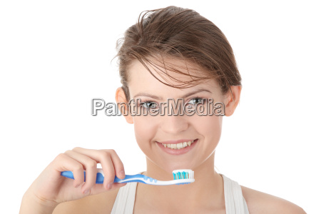 young girl brushing her teeth happily