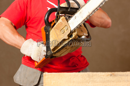 construction worker or handyman with chainsaw