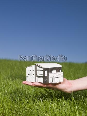 man holding a miniature house outside