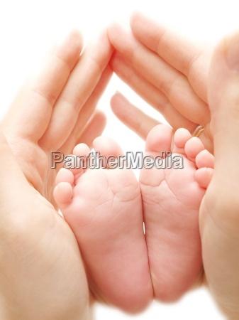 baby feet between grownups hands