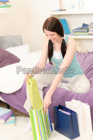young happy student unpack shopping bags