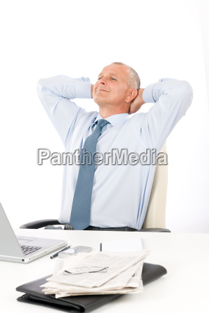 happy businessman relaxing in office behind
