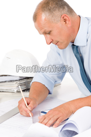 professional architect with blueprint behind table
