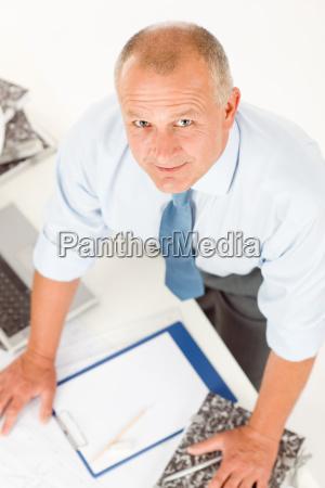 senior man standing above office table