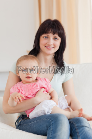 charming woman holding her baby in