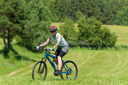 sport mountain girl biking uphill sunny