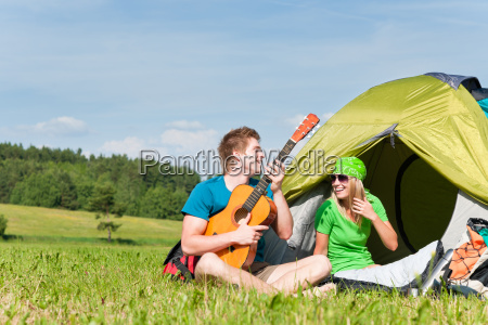 camping couple playing guitar by tent