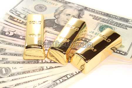 three gold bars on dollar bills