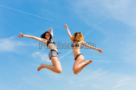 two happy women jump high with