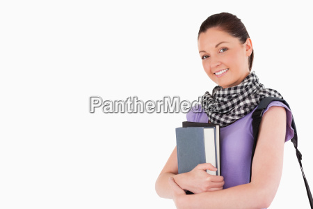 good looking student holding books and