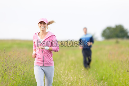 jogging sportive young couple running meadow
