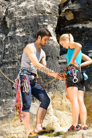 rock climbing man showing woman rope